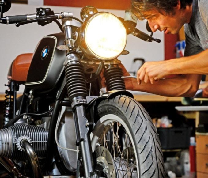 Un homme bricole une moto